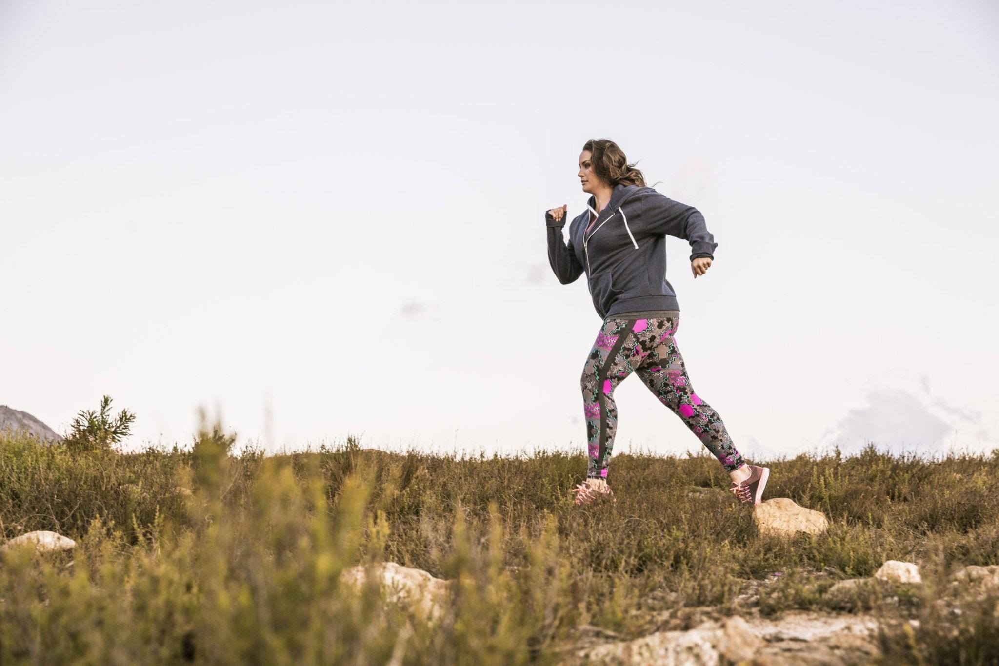 Frau mit kräftigen Beinen läuft auf einer Wiese