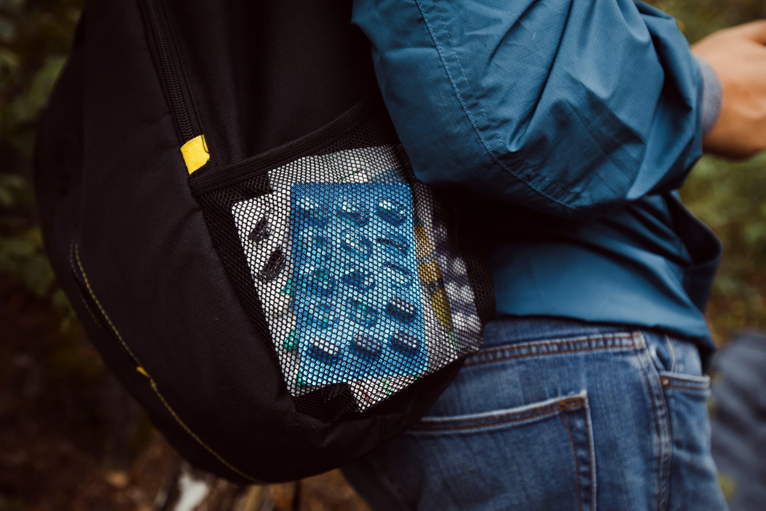 Eine Person steht und trägt einen Rucksack. In der Seitentaschen sind Tabletten.