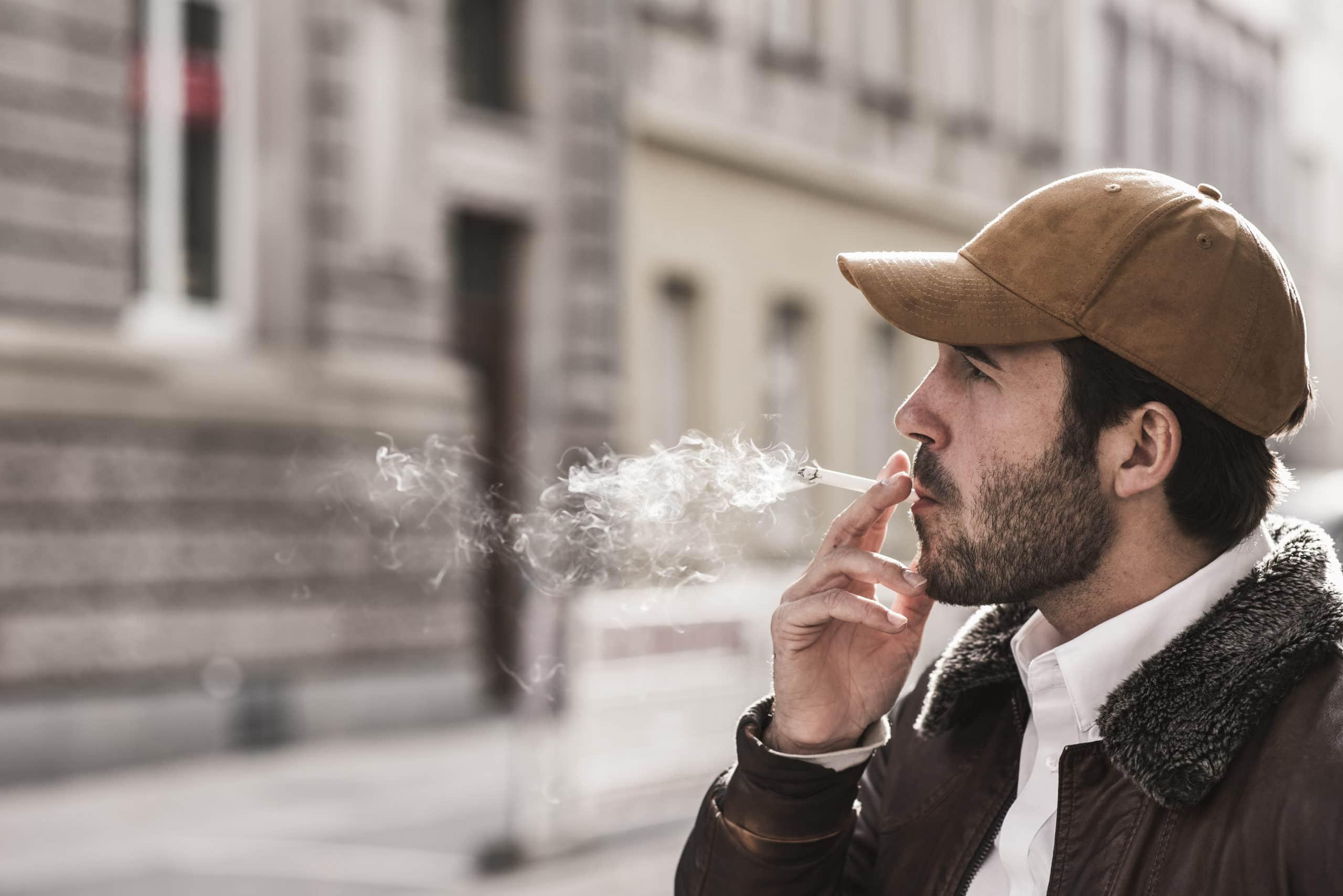 Mann mit Kappe raucht auf der Straße