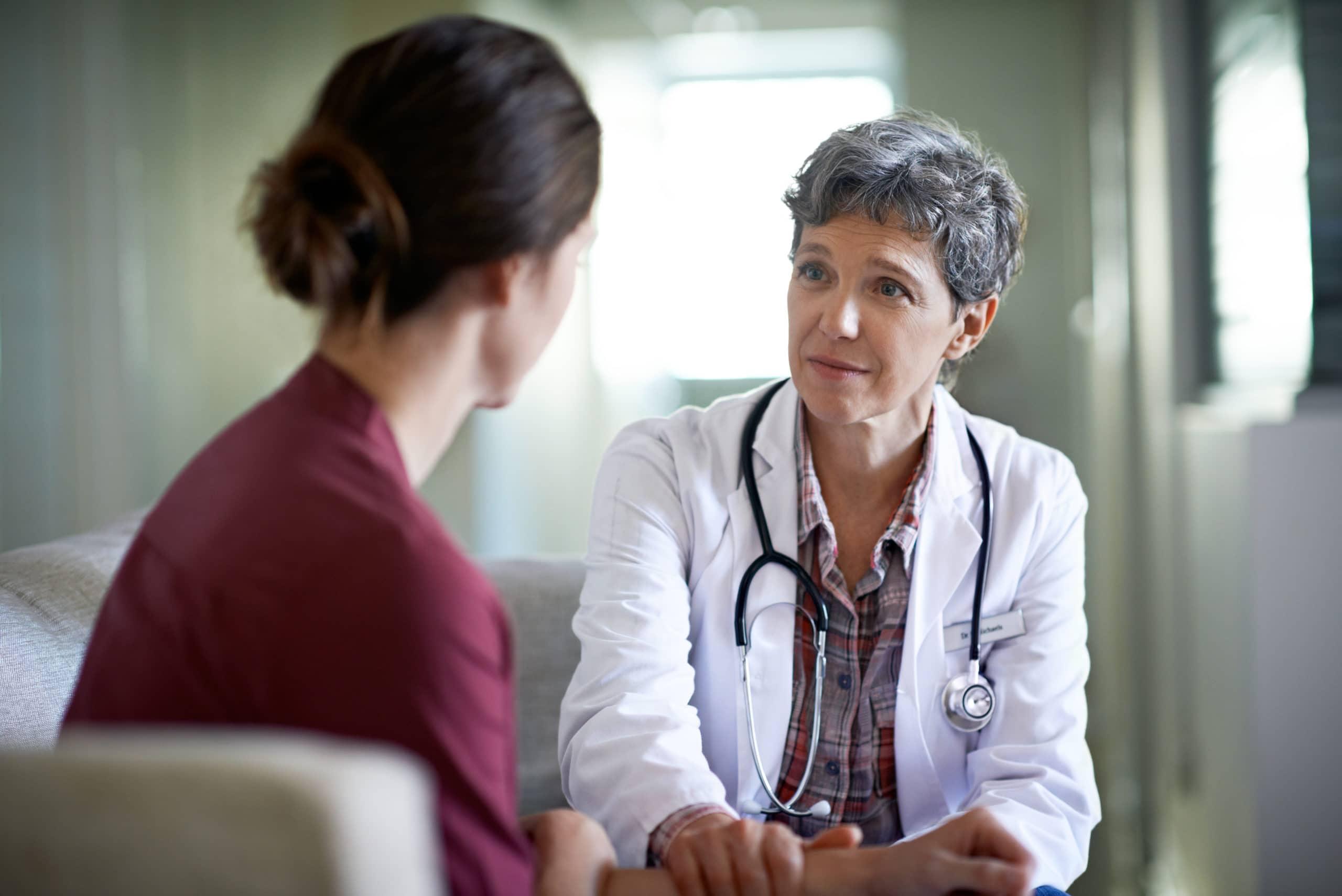 Eine Ärztin mit besorgtem berät ihre Patientin