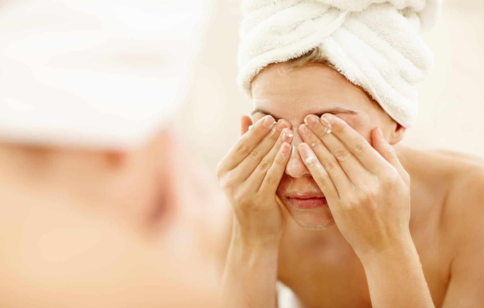 Eine Frau mit Handtuch auf dem Kopf wäscht sich das Gesicht