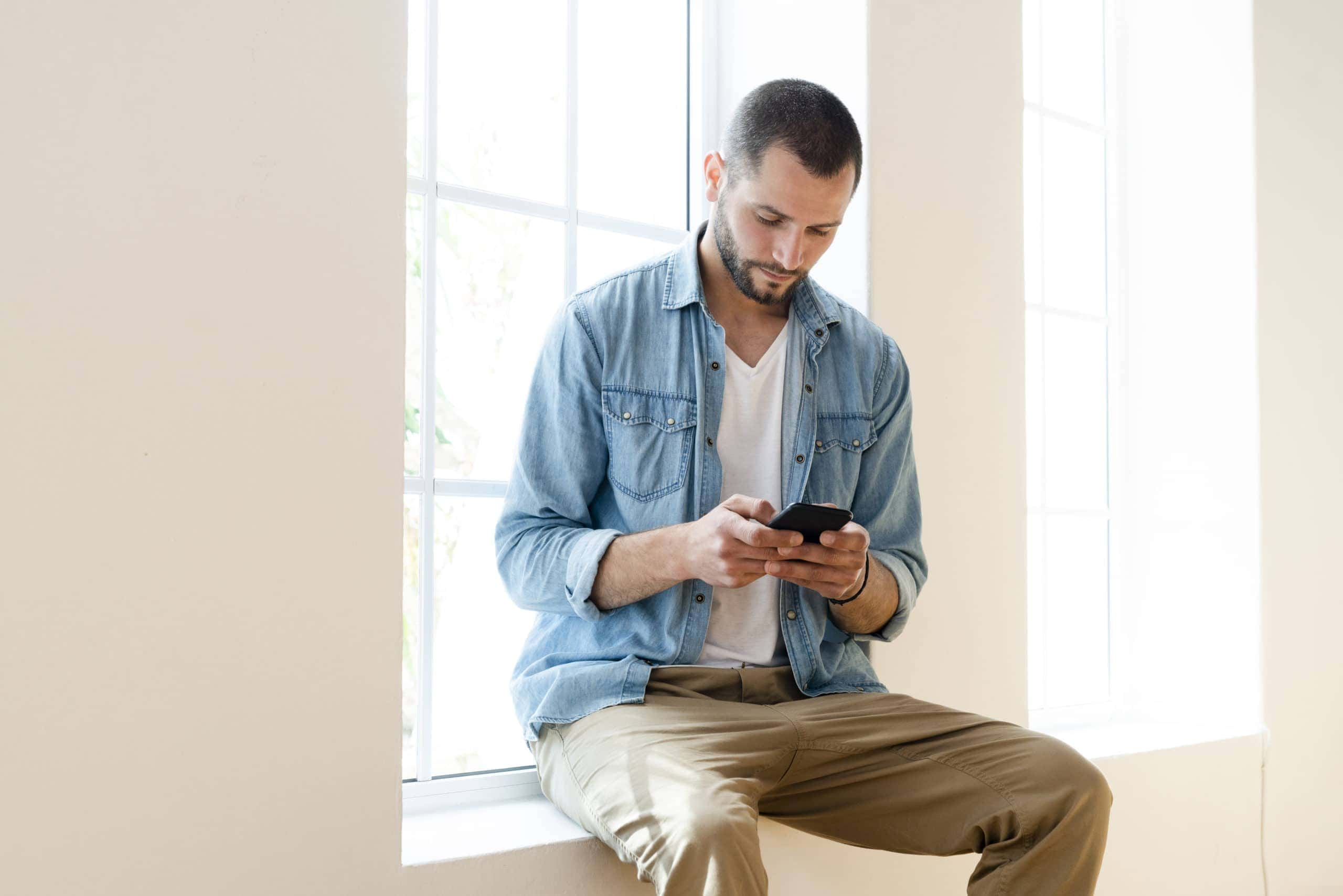 Ein junger Mann schaut sitzt auf einem Fensterbrett und schaut ernst auf sein Smartphone