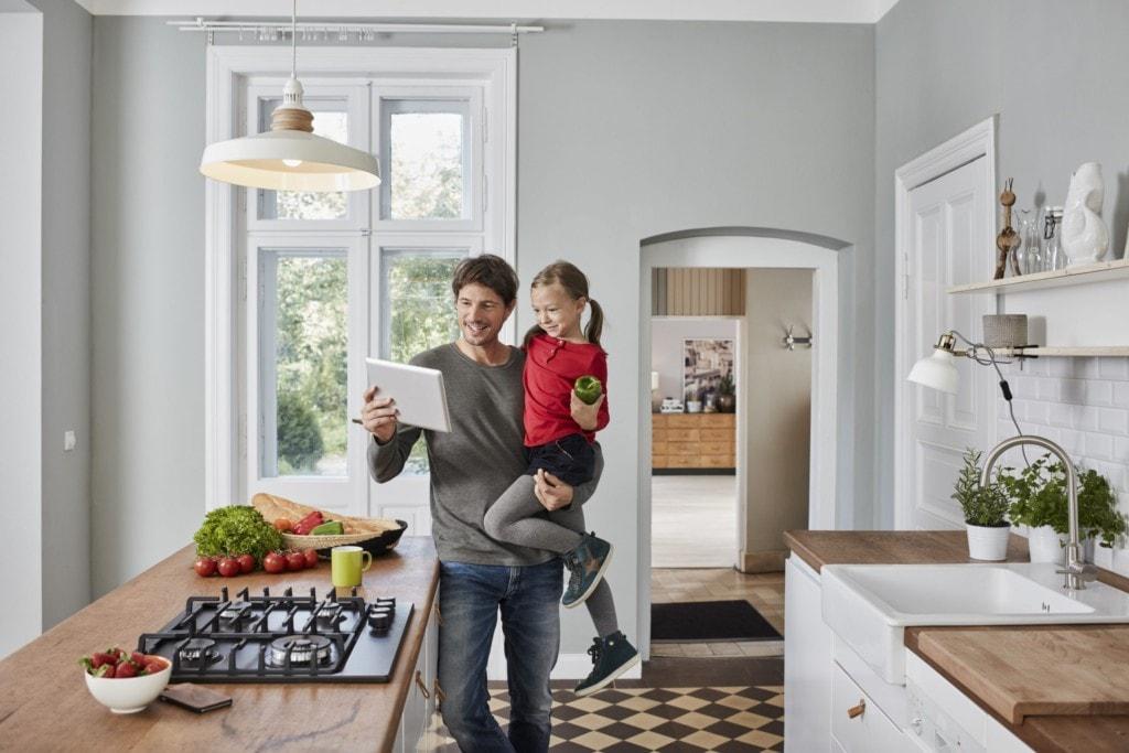 Ein Vater und seine Tochter tragen ein Tablett und Paprika in der Küche