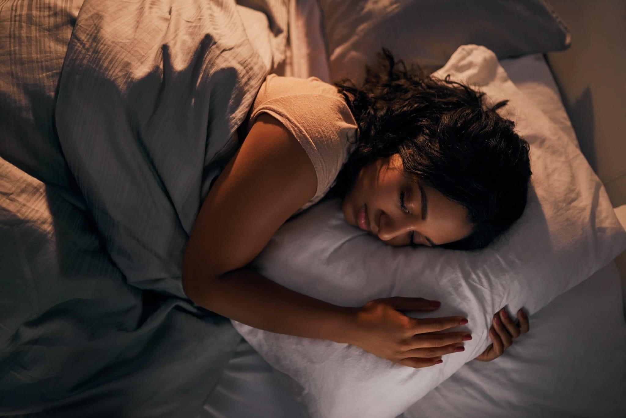 Eine Frau schläft nachts in ihrem Bett