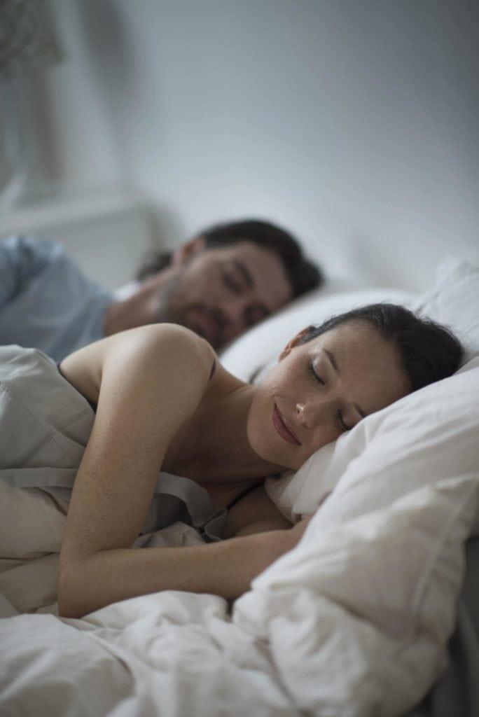 Paar schläft nebeneinander im Bett