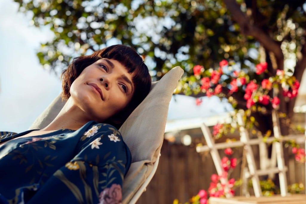 Frau liegt in einem Gartenstuhl