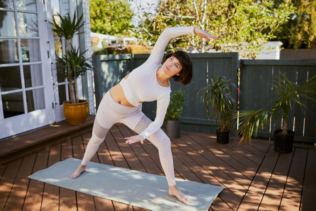 Young woman practicing yoga alone on her patio at home