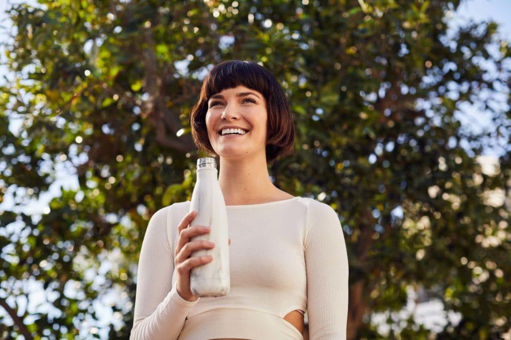 Lachende Frau in Sportkleidung steht nach Workout in ihrem Garten und hält eine Wasserflasche