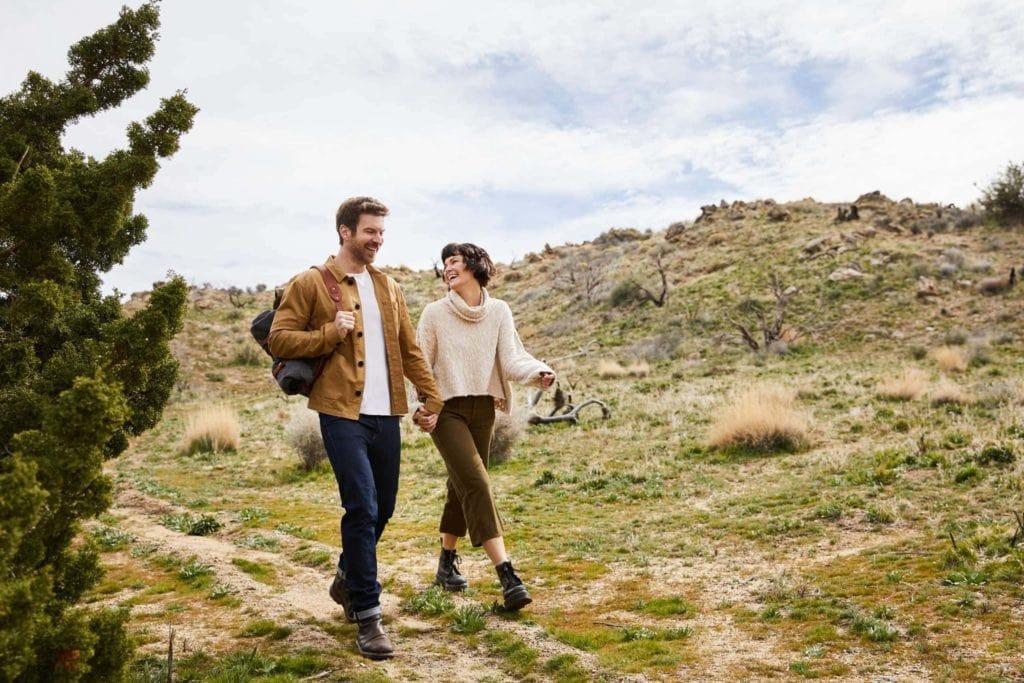 Lachendes Paar hält beim Wandern in der Natur Händchen