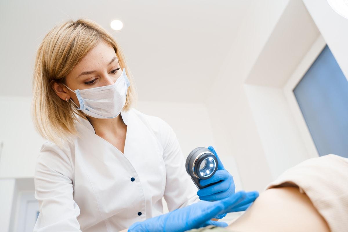 Eine Ärztin untersucht mit einer Lupe die Haut eines Patienten.
