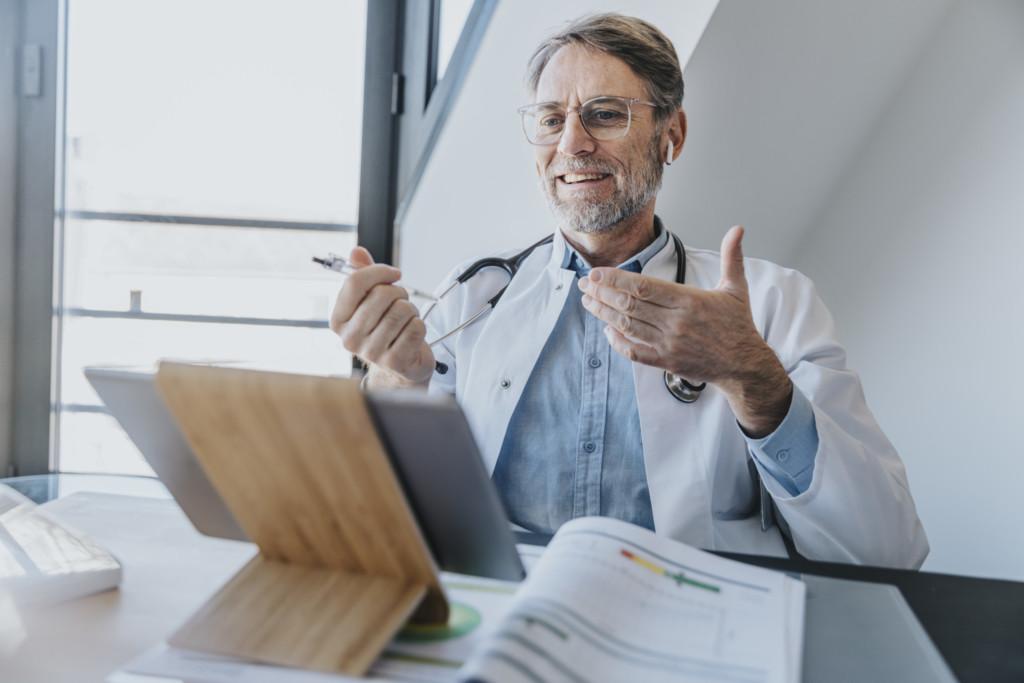 Ein Arzt führt einen Ärzte-Videochat am Tablett durch.