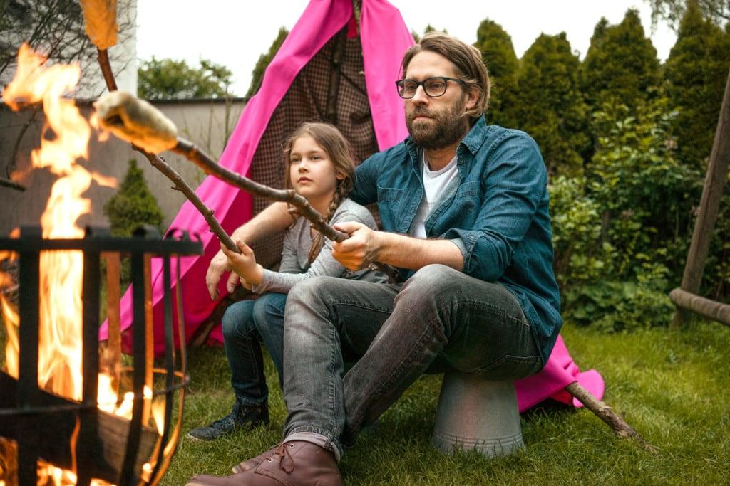 Ein junger Vater mit Bart und Brille sitzt mit seiner Tochter vor einem Zelt am Lagerfeuer. Sie halten Stockbrot ins Feuer.