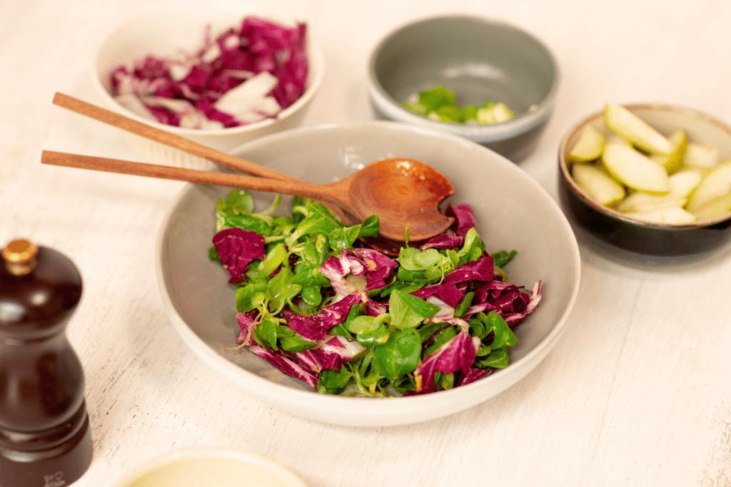 Der Salat in einer Schüssel, daneben die einzelnen Zutaten in kleinen Schlüsseln