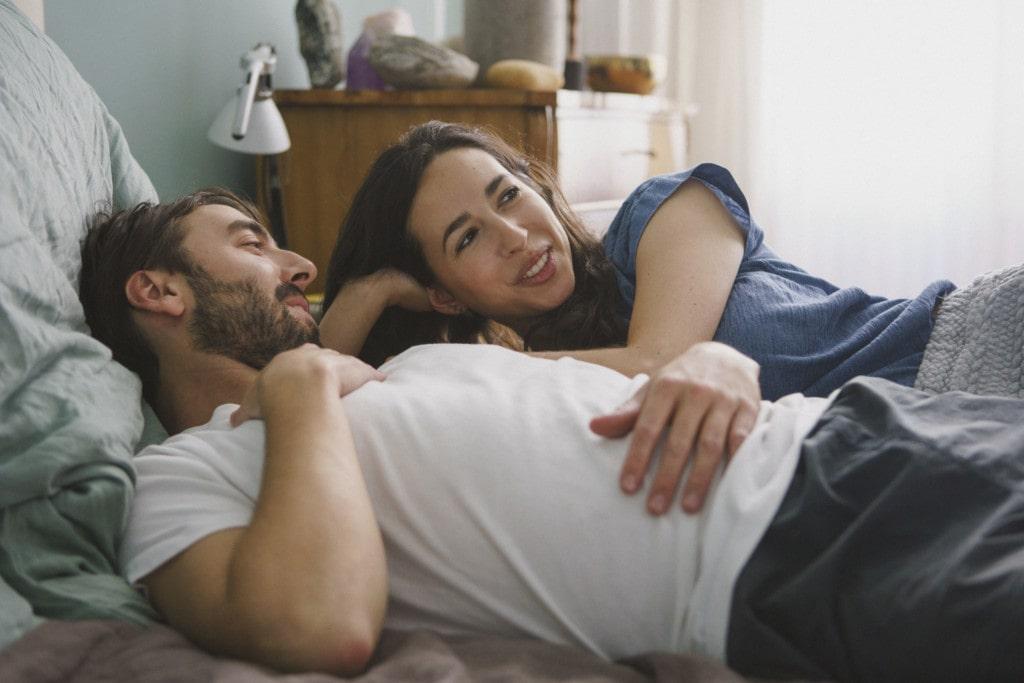 Ein Paar liegt im Bett und unterhält sich