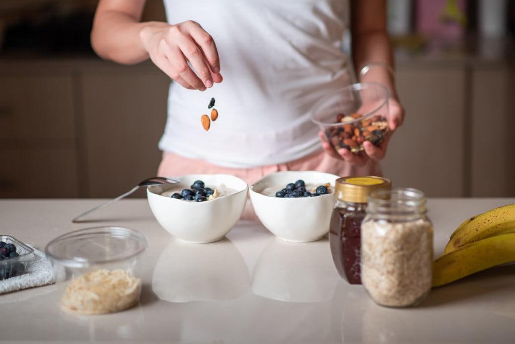 Eine Frau fügt Nüsse ihrem Porridge zu