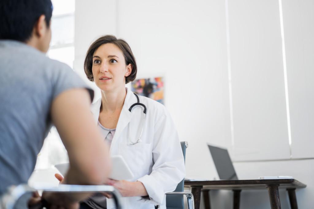 Eine Ärztin mit einem Tablet spricht mit einem Patienten über seine Blutwerte